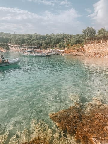 Turquoise water surrounded by rocks and beach front bars. What to do in Hvar