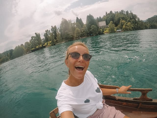A woman taking a selfie in a rowing boat at lake bled