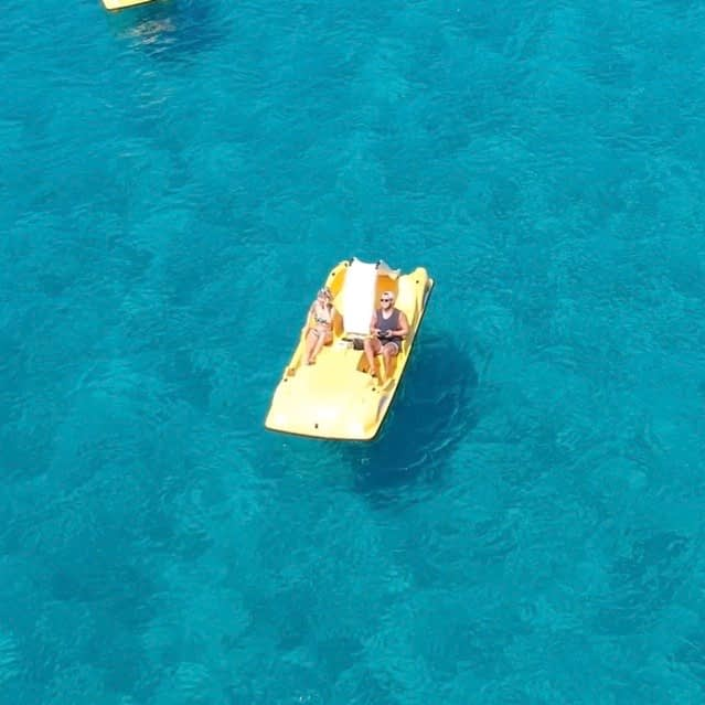 Couple on a pedal boat in the sea as part of the lassi, kefalonia guide.