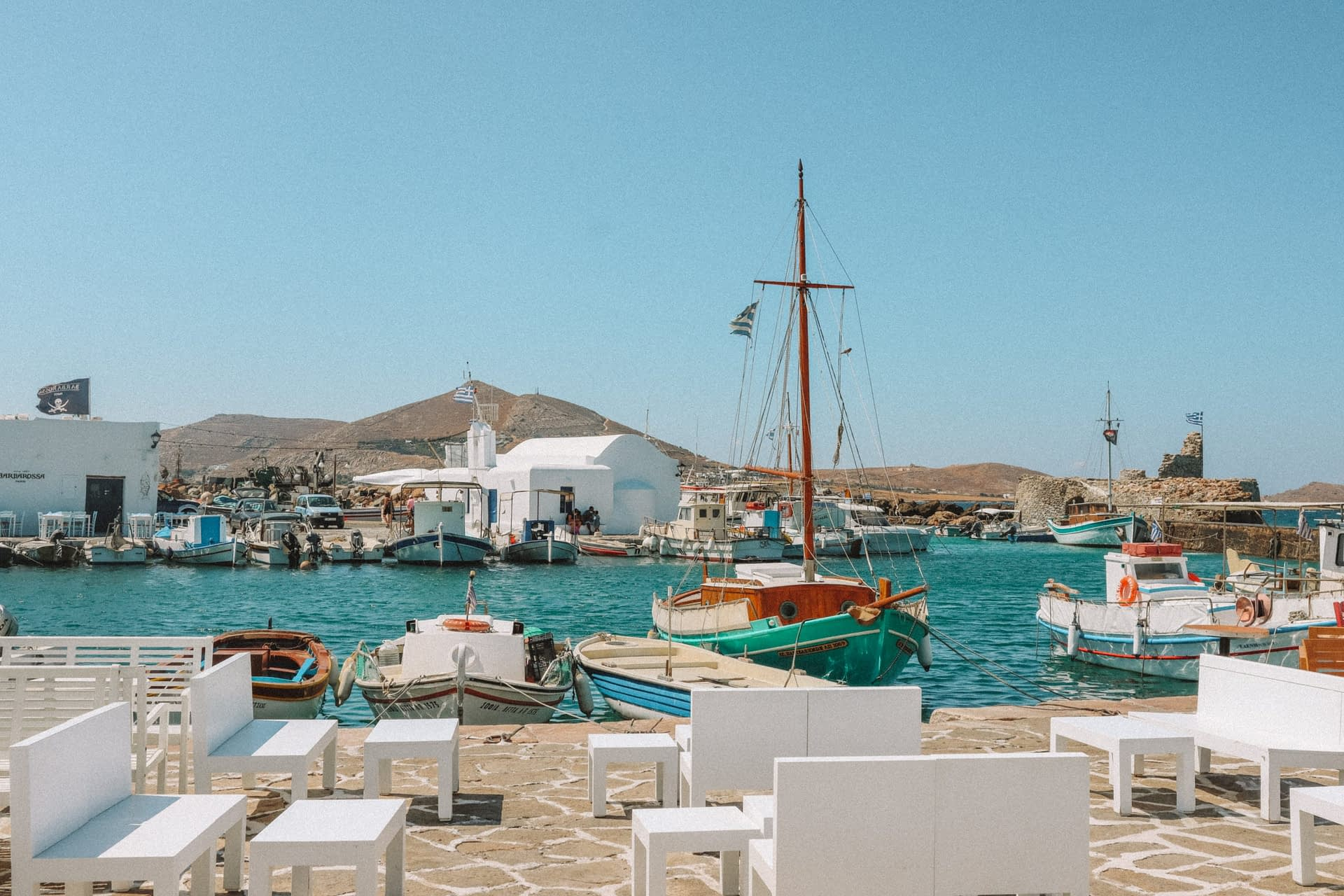 Docked boats in turquoise water at the Naoussa harbour. Things to do in Paros