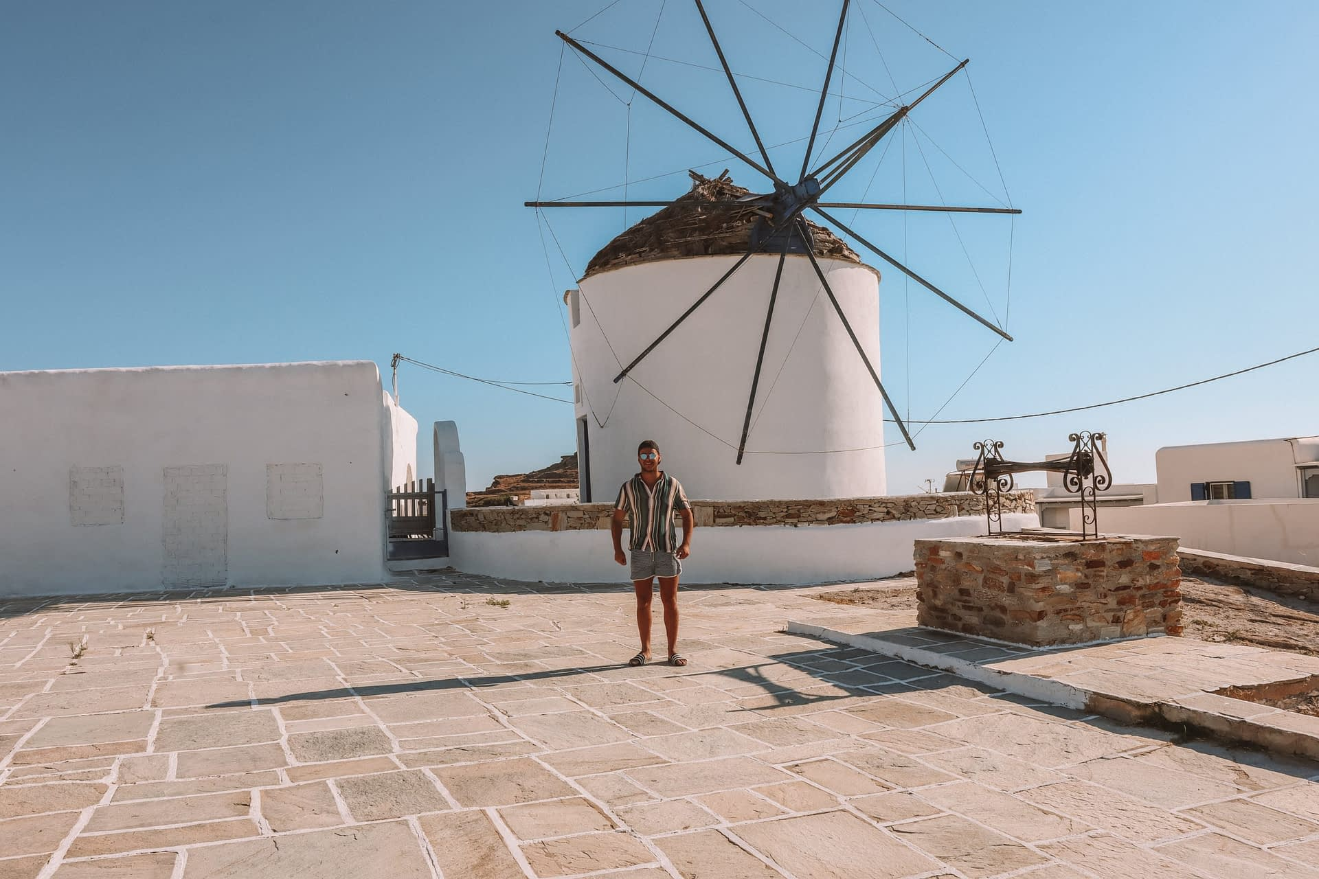 A man carrying invisible carpets in front of a windmill in Ios