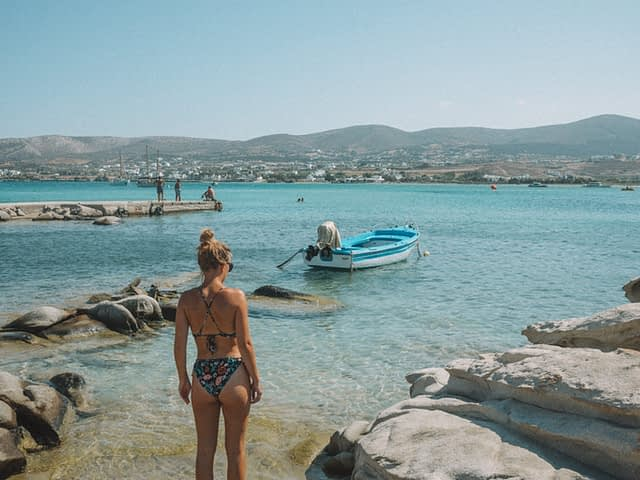 A woman stood by Kolymbithres beach and a boat