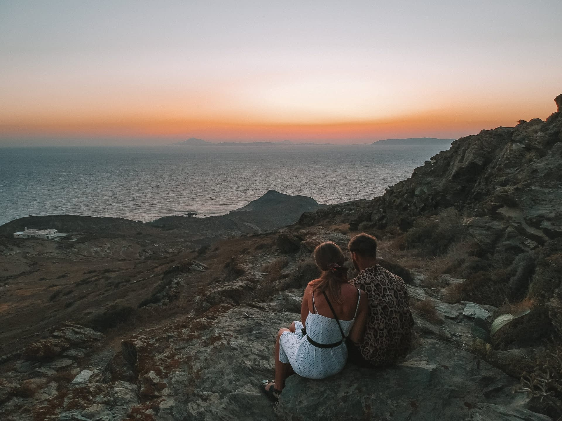 A couple sat on a rock during sunset. What to do in Folegandros