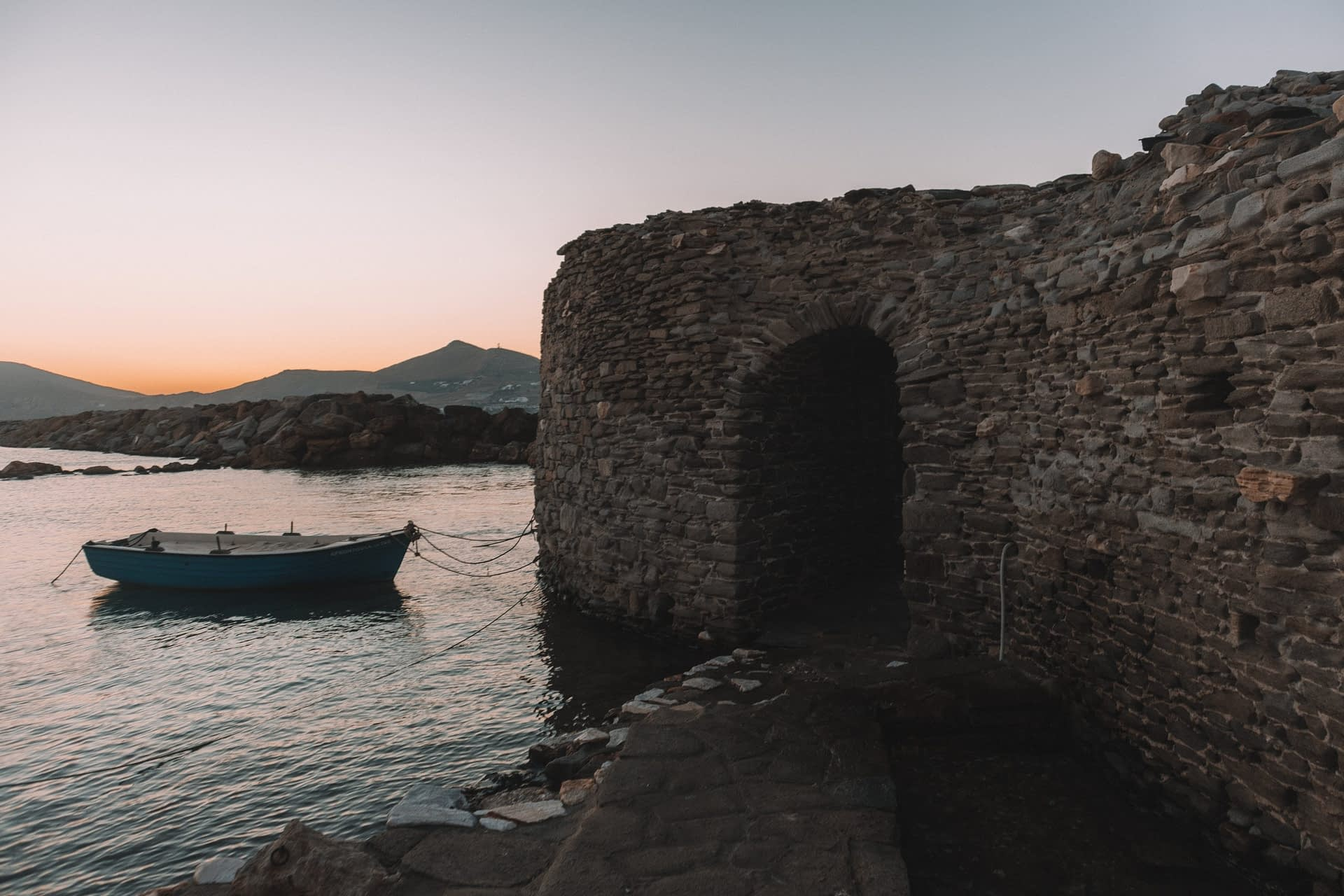 Naoussa venetian castle at sunset with a boat in the background. Paros travel blog