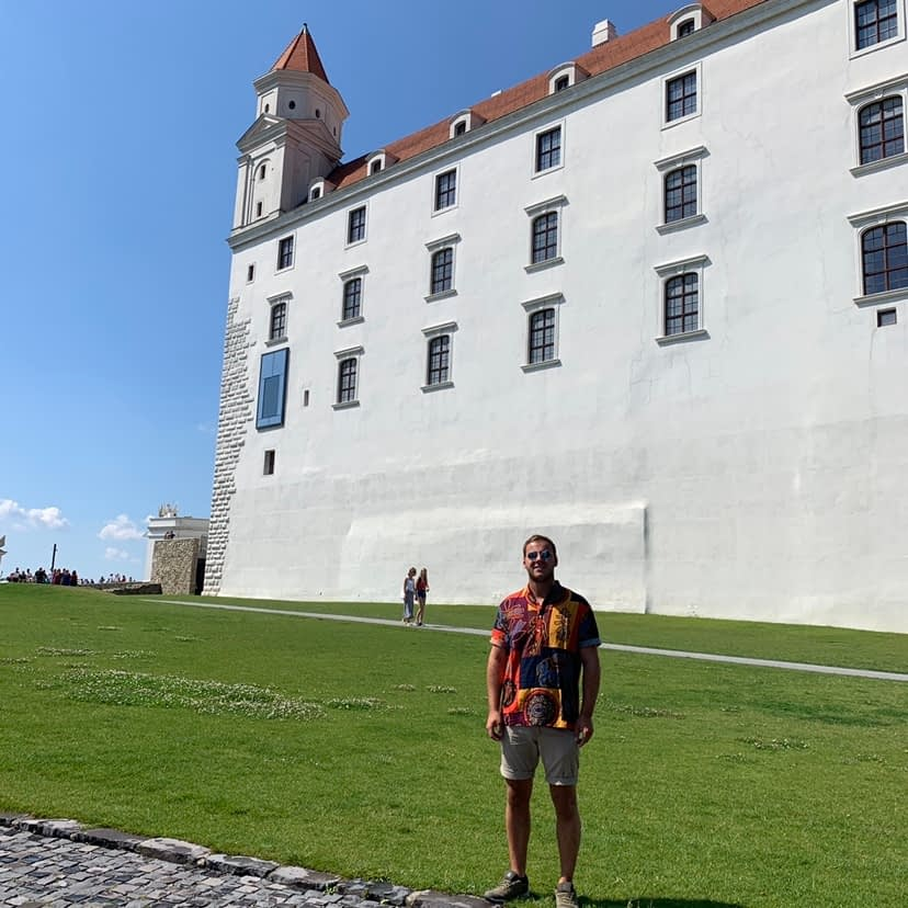 A man stood in front of the Bratislava castle. Advised to visit from the Bratislava travel guide.