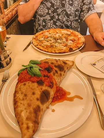 Tomato calzone pizza and a seafood pizza with beer. Venice in a day