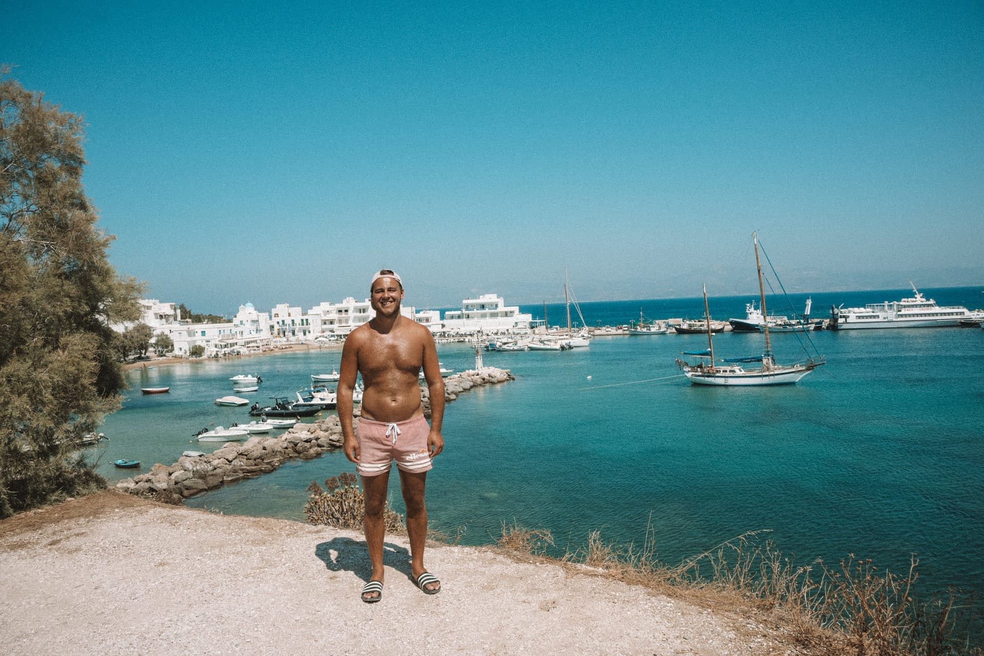 A man stood in front of the harbour of Piso Livadi. What to do in Paros