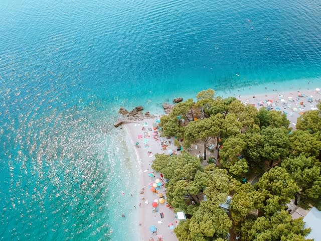 An aerial view of the coast in the Croatian Riviera. Turquoise waters and pine trees.
