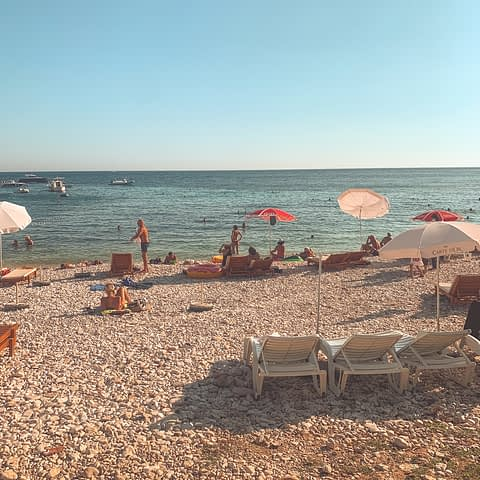 Milna beach with deck chairs and pebbles with turqoise water nearby. Best beaches in Hvar