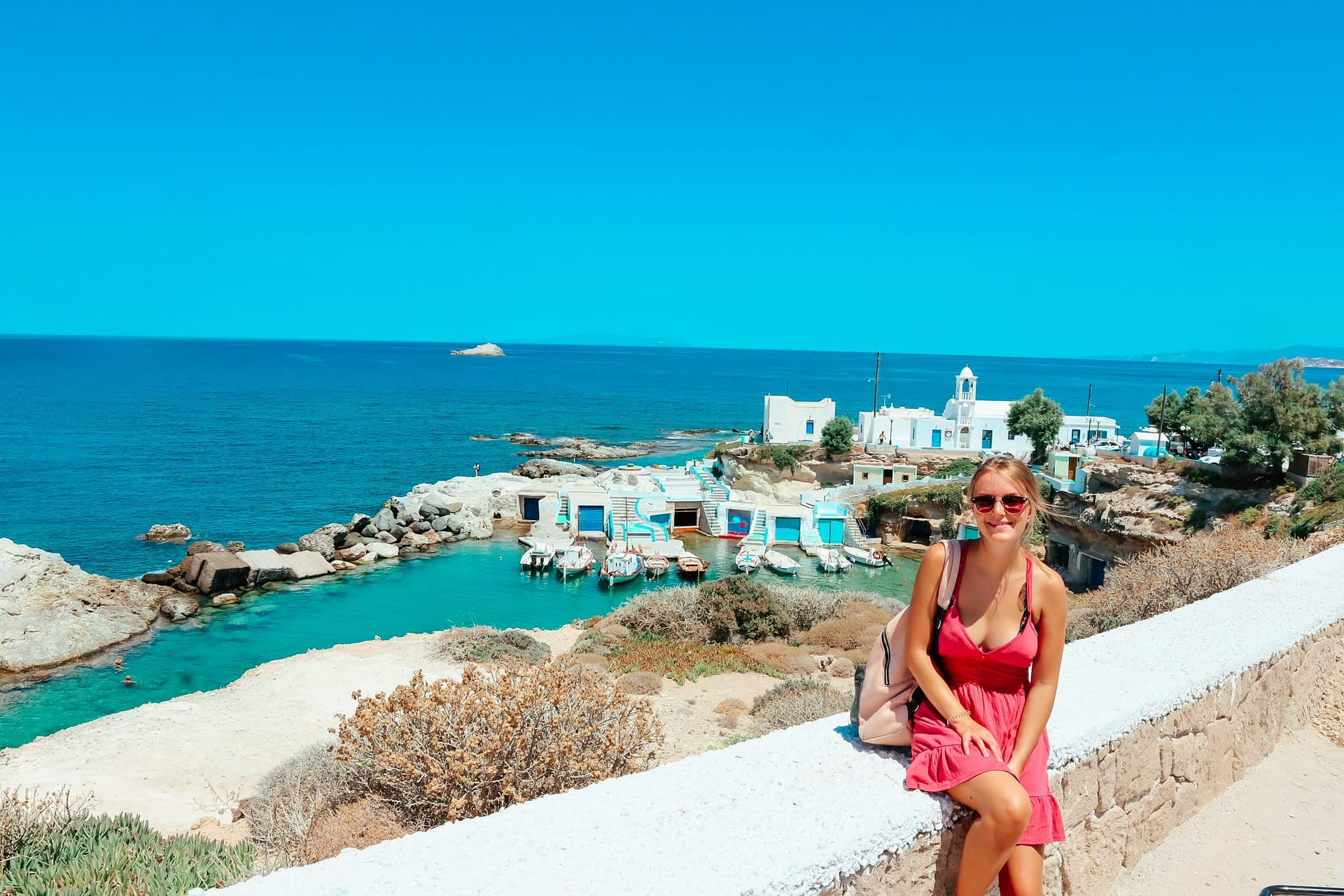 A woman sat on a wall with Mandrakia village in the background. Milos travel guide