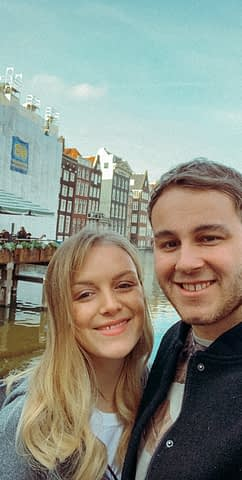 A couple taking a selfie in front of different buildings in Amsterdam