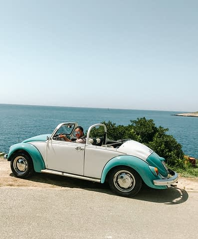 A man in a 60's white and blue VW convertible with the sea in the background. Things to do in Hvar