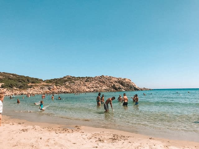 People splashing in the turquoise ocean and on the sand. What to do in Sardinia