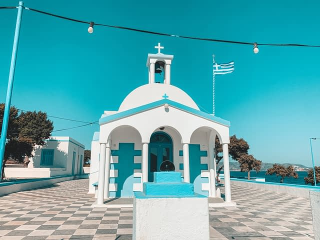A blue and white painted church with a blue sky in the background. Things to see in Milos