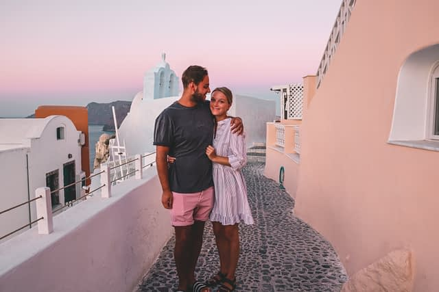 A couple stood next to pastel coloured buildings and a pink sky at sunrise.