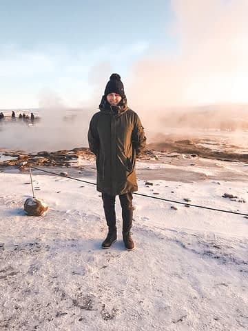 A man in front of a snowy Stokkur Geyser. Things to do in Iceland