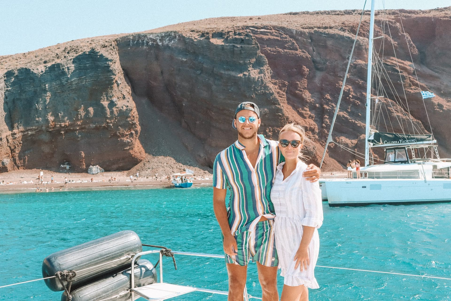 A couple stood on a boat with turquoise water and the red beach in the background. Things to do in Santorini