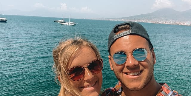 A couple taking a selfie with boats, ocean and mountains in the background. Things to do in Naples