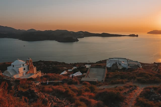 Plaka during sunset which a church. Things to see in Milos