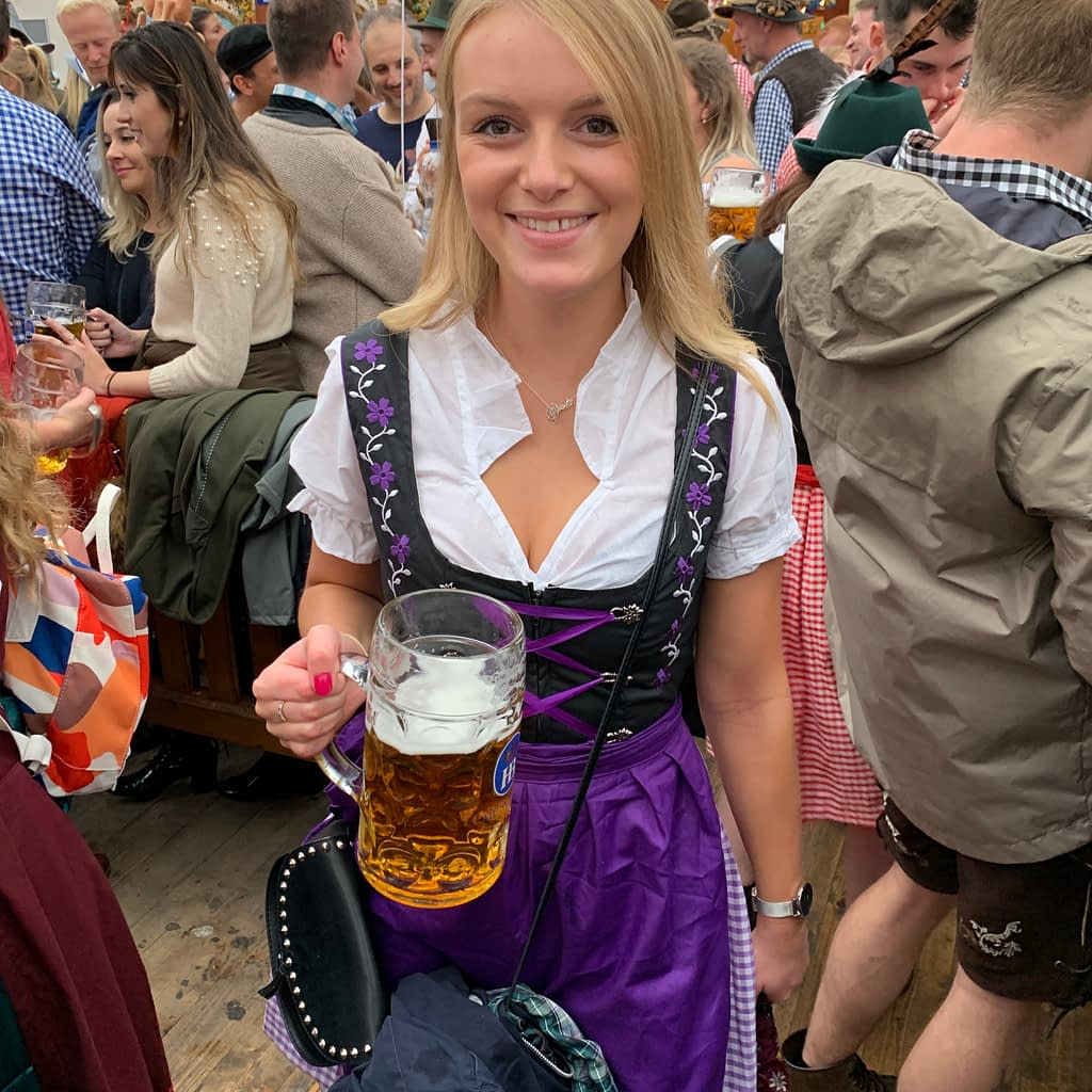 A woman in a dirndl and with a beer.