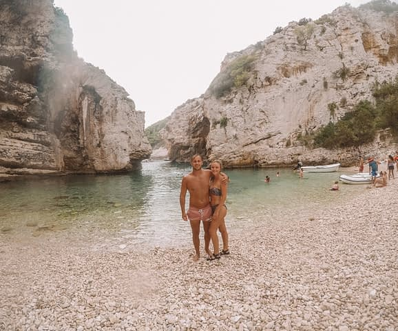 A couple on a pebble beach with a cave surrounding. Things to do in Hvar