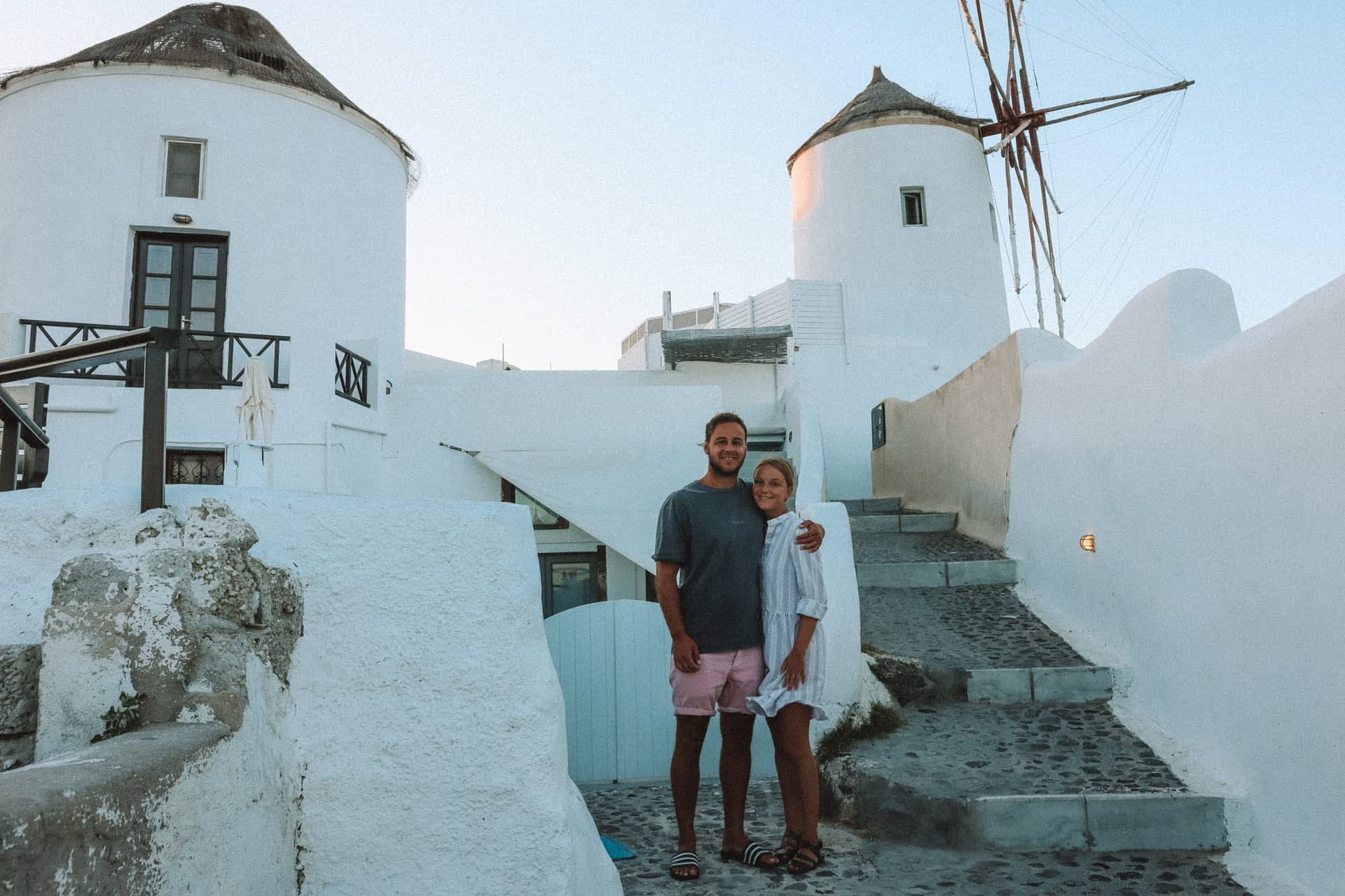 A couple stood in front of two windmills in Santorini