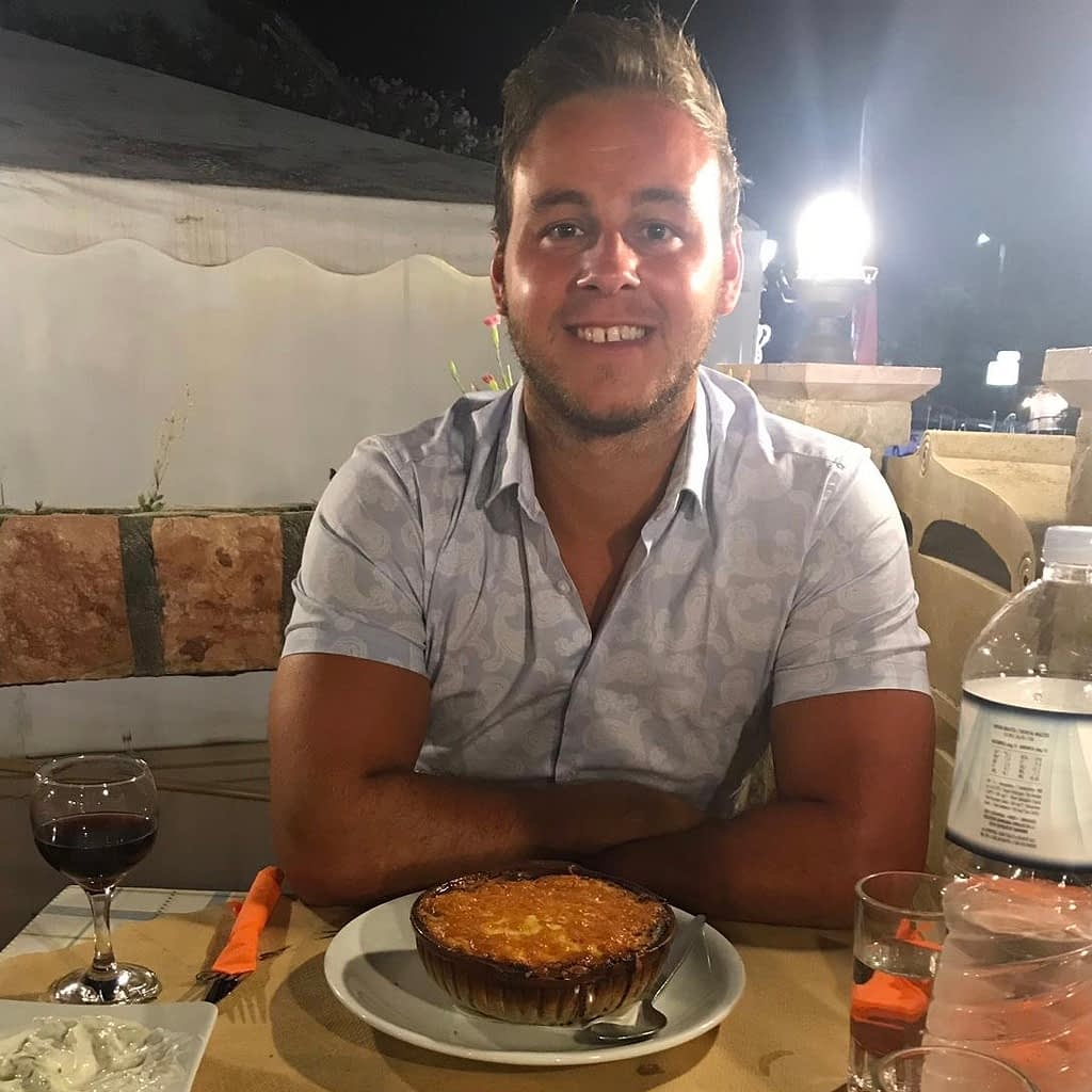 A man with some moussaka at a restaurant.