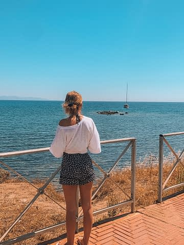 A woman looking at a boat in the ocean. Things to do in Sardinia