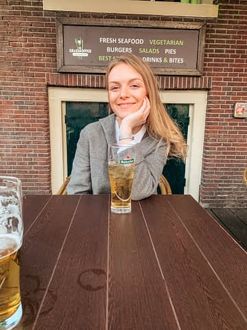 A woman sat at a table with a Heineken beer.