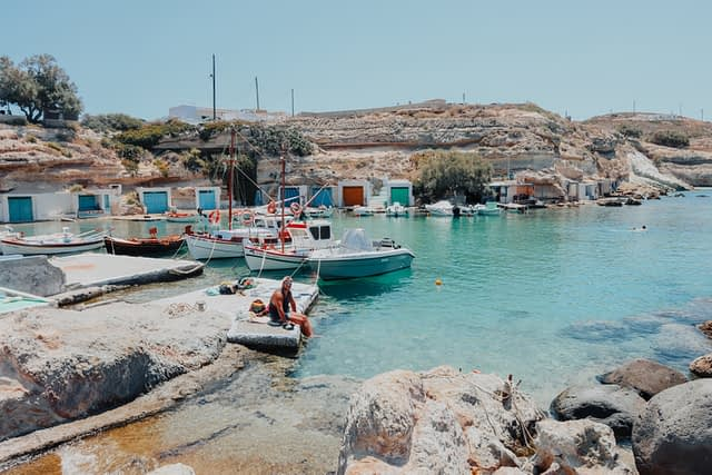 A man sat next to boats and colourful boathouses in Milos