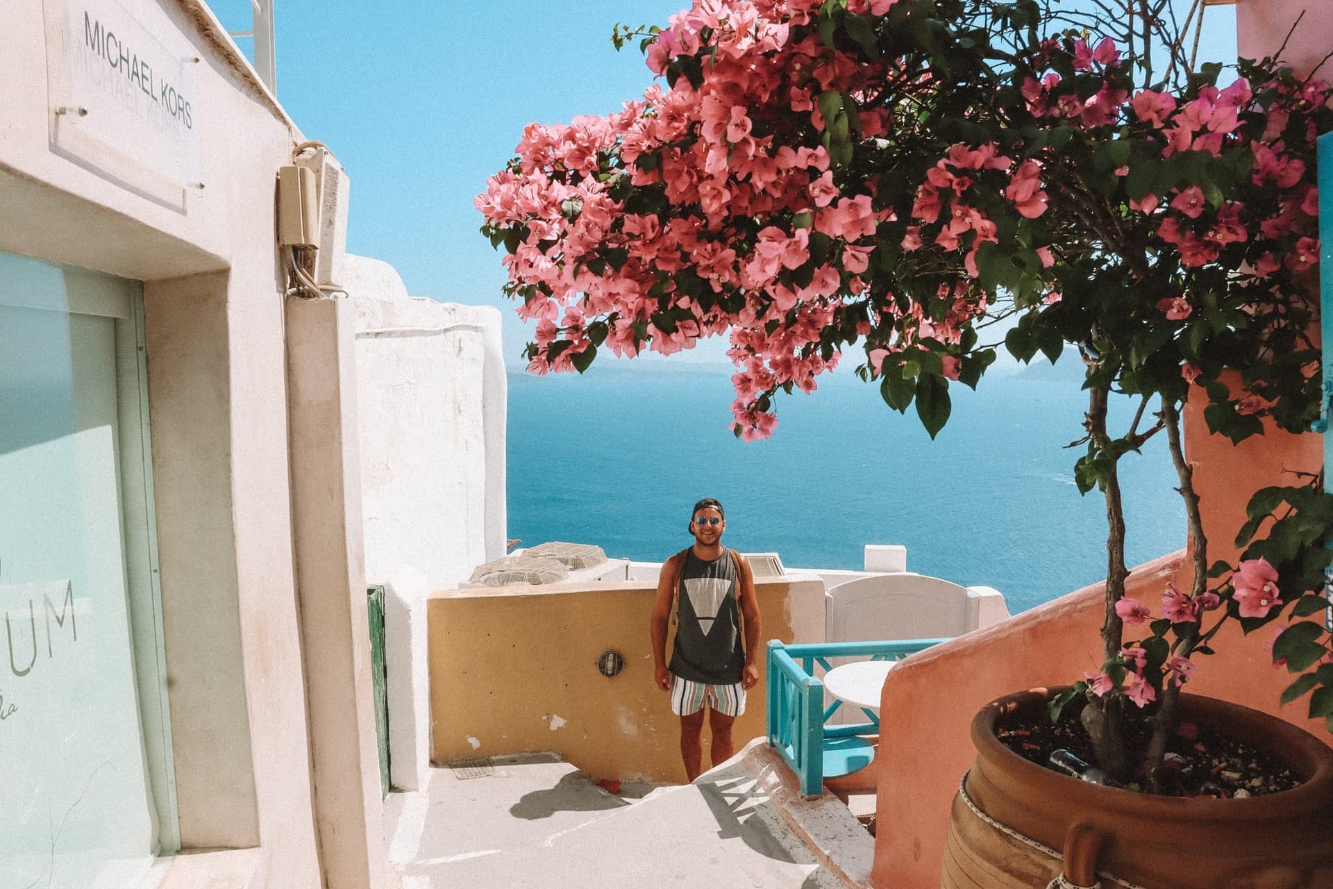 A man stood near pastel coloured walls with a tree blossoming. Things to do in Santorini