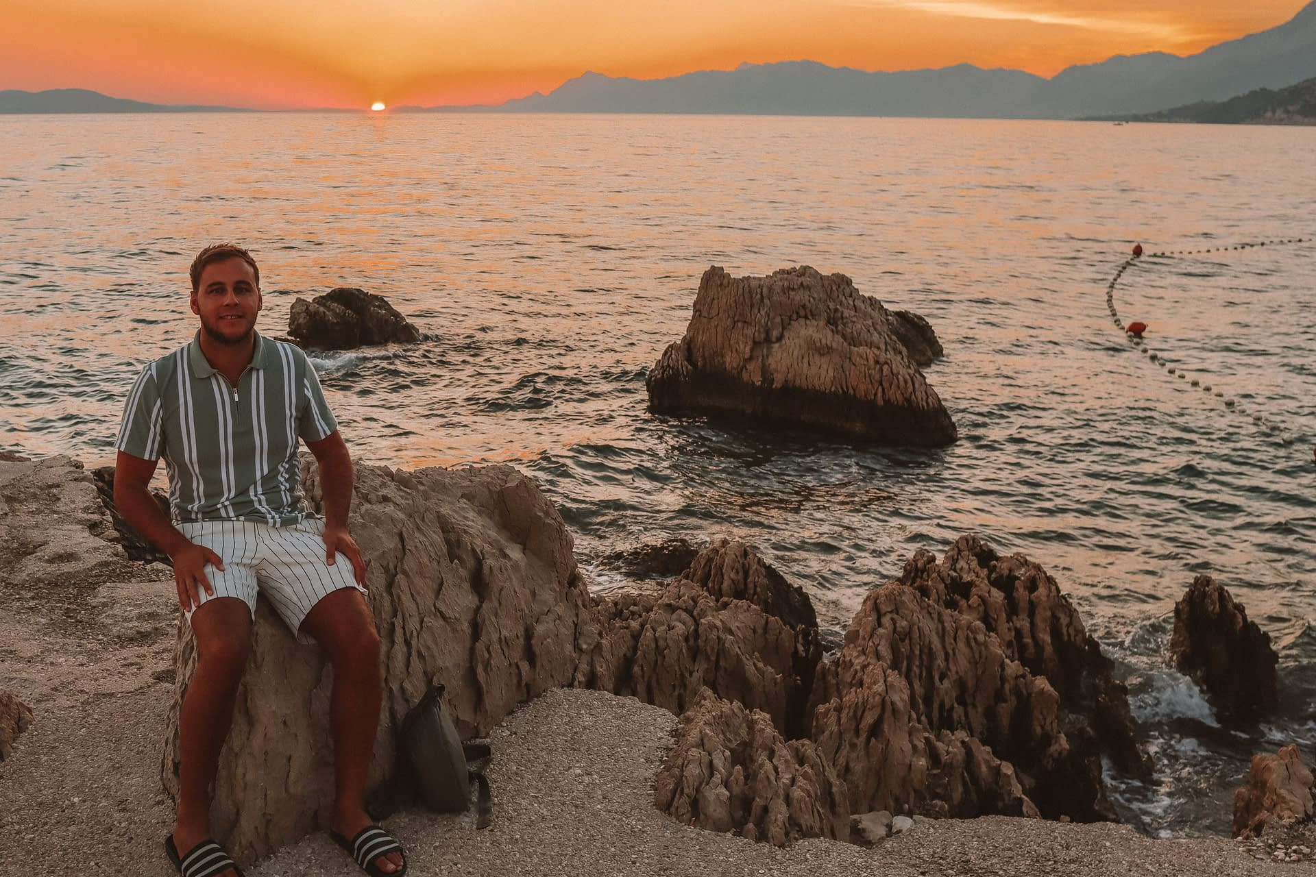 Man sat on rocks during the sunset with the ocean in the background