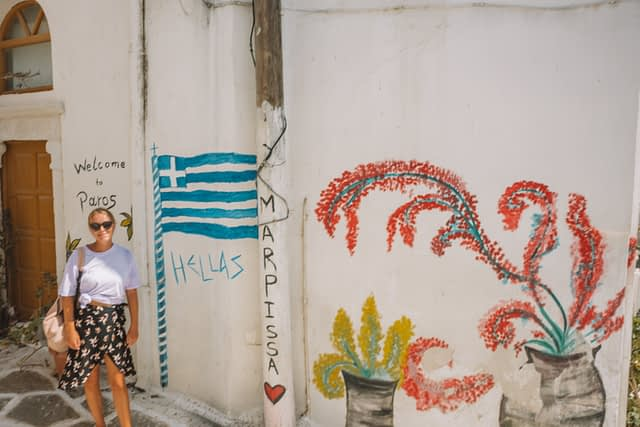 A woman stood in front of wall art in Marpissa, paros