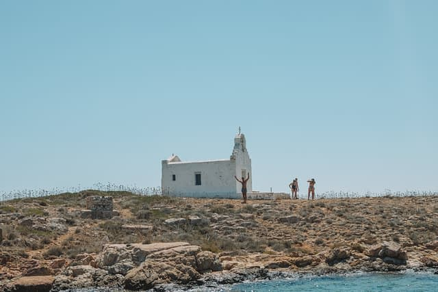 A man infront of a white church on an island. Things to do in Paros