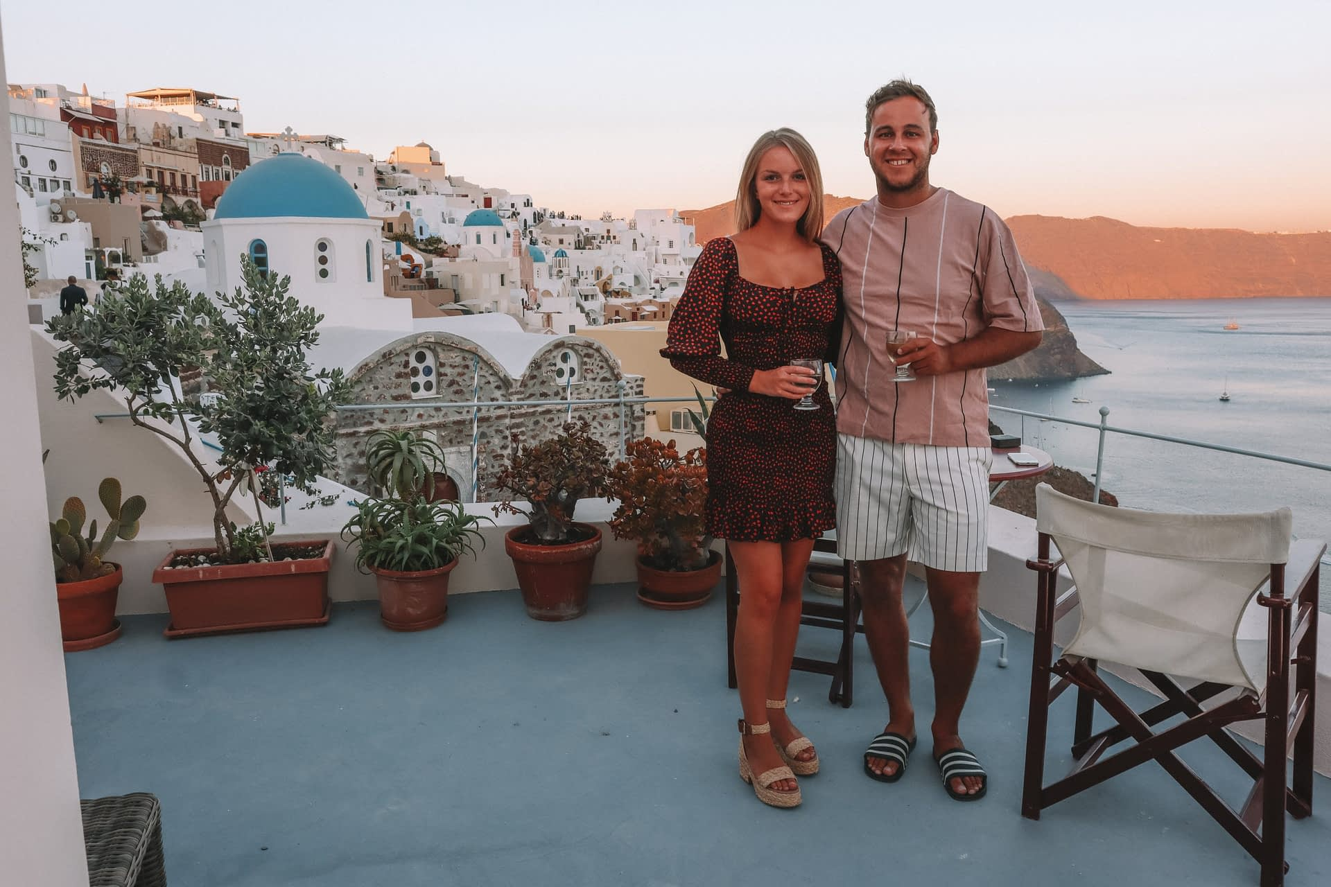 A couple stood on their balcony with blue domed churches and ocean in the background in Santorini