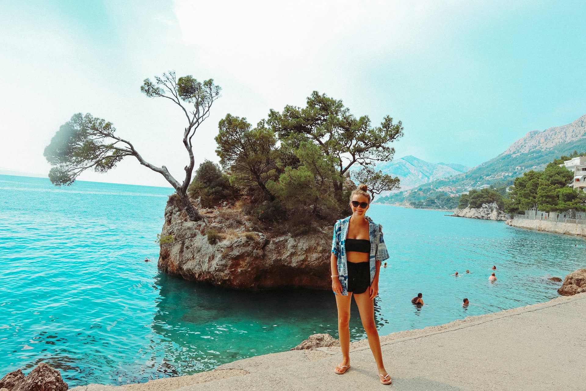 A woman stood in front of Kamen Brela. Your guide to the Croatian Riviera