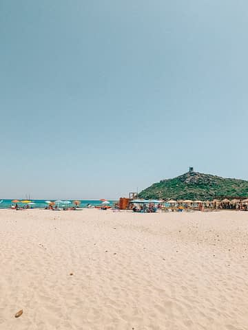 Poro Giunco beach from a far with a castle in the background. One of the many Sardinia beaches