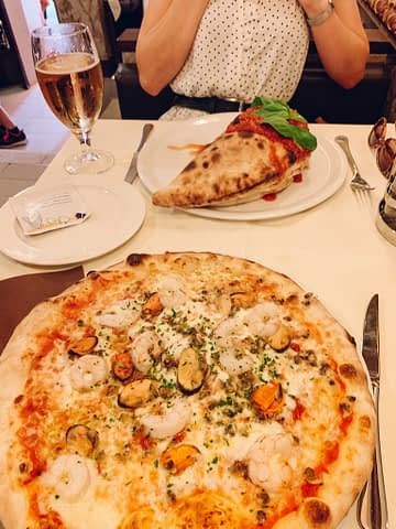 Seafood pizza and a Calzone pizza with wine. What to do in Venice