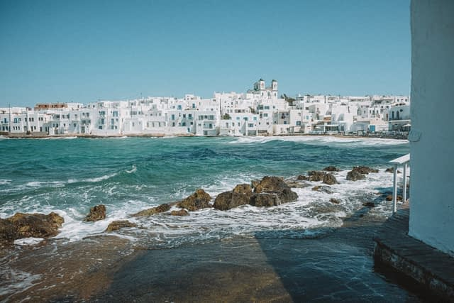 The sea and rocks with whitewashed buildings in the background of Naoussa. Paros travel blog