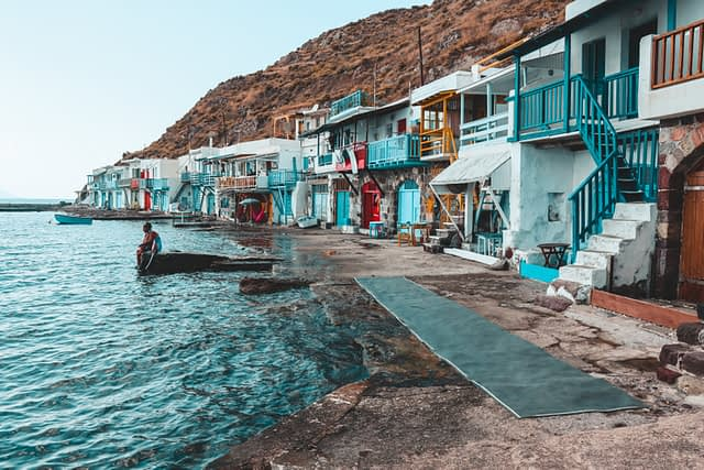 Colourful fishing area at Kilima in Milos. A man sits looking to the ocean. Things to do in Milos.