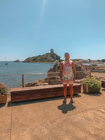A man stood near the ancient Nora ruins with a castle and ocean in the background. Sardinia beaches