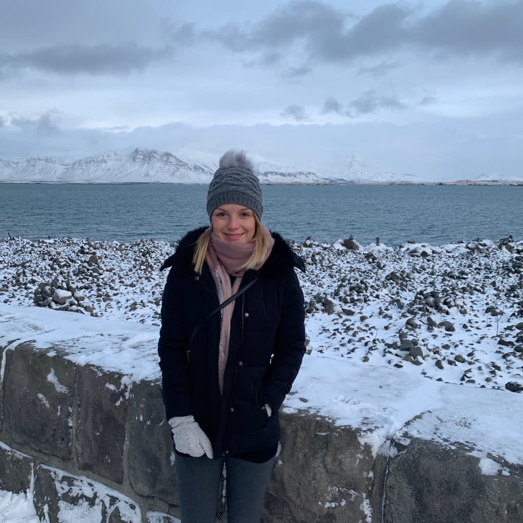 Woman stood in front of the sea in Reykjavik.