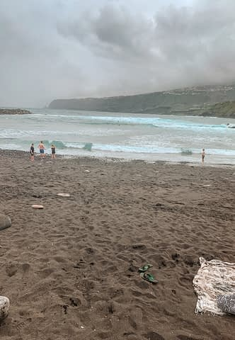 Black sandy beach with blue waves. Things to do in Tenerife