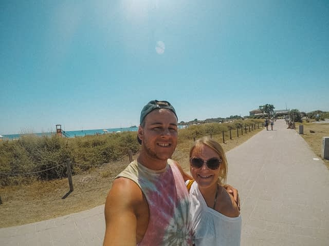A couple taking a selfie on the road near a beach in Sardinia