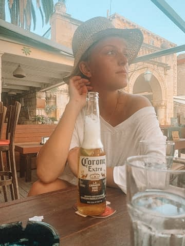 A woman in a straw hat sat drinking a bottle of Corona at a table. What to do in Hvar