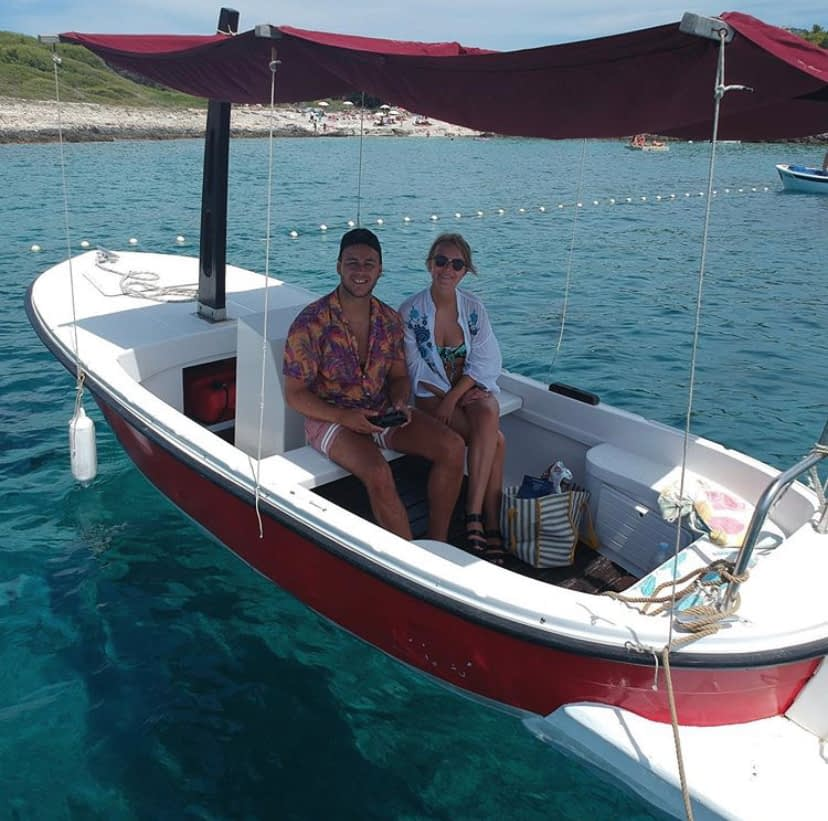 A young couple in a boat as part of the things to in Hvar.