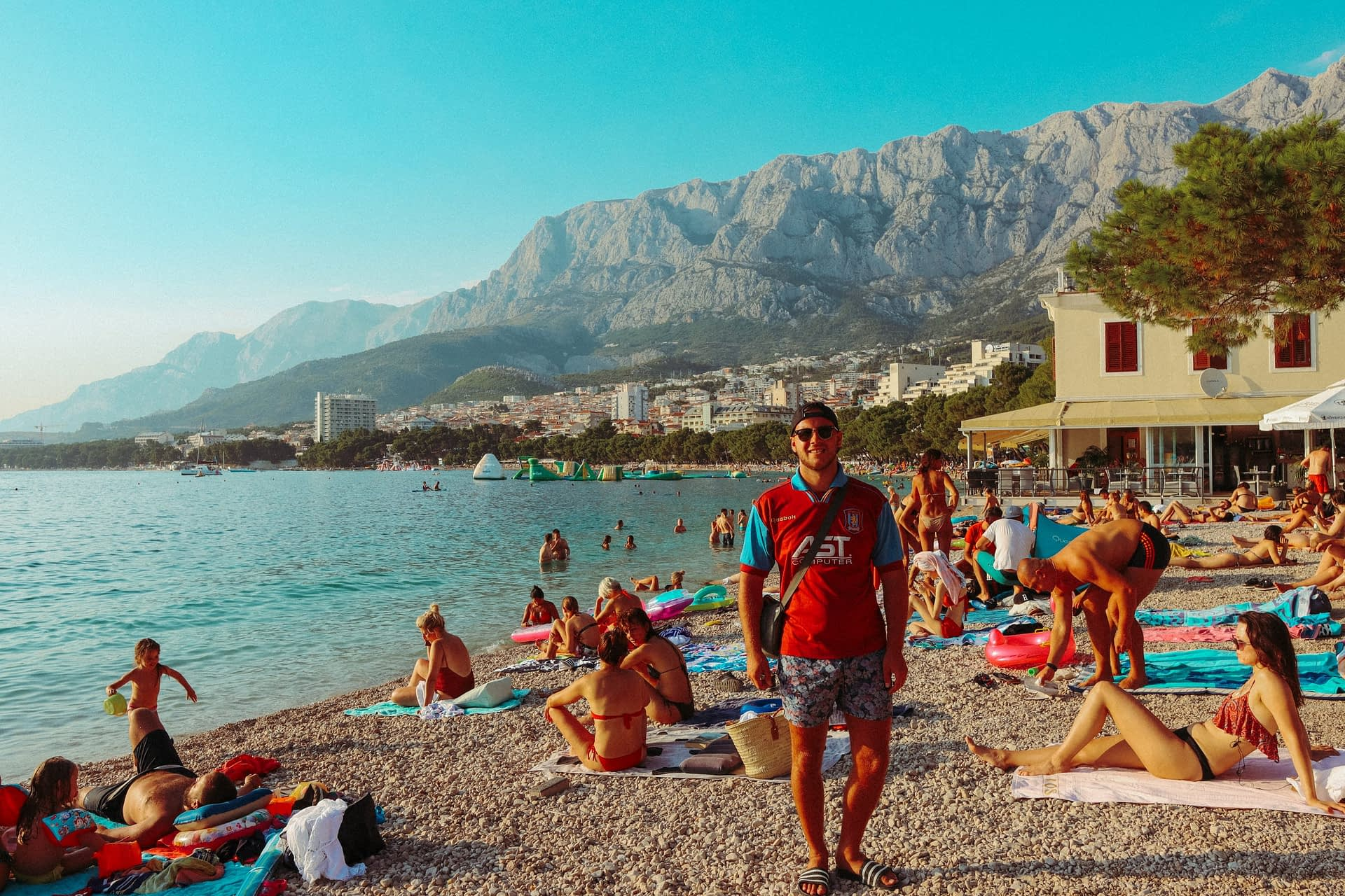 A man stood on a busy pebble beach with Mount Biokovo in the background. Things to see in Makarska