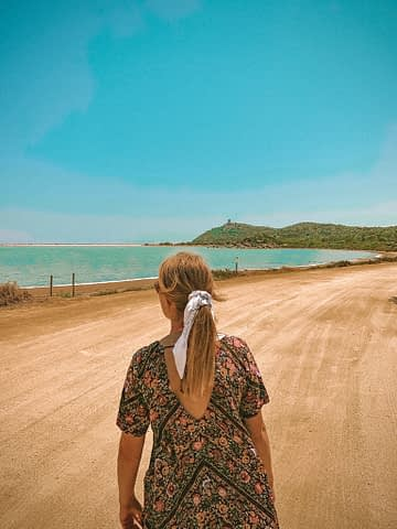 A woman walking to the beach and sea in Sardinia.
