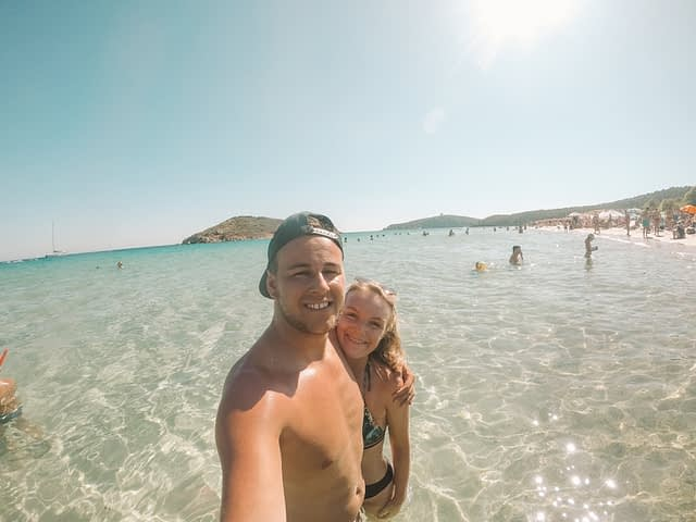 Things to do at Tuerredda beach. A couple in the sea taking a sefie