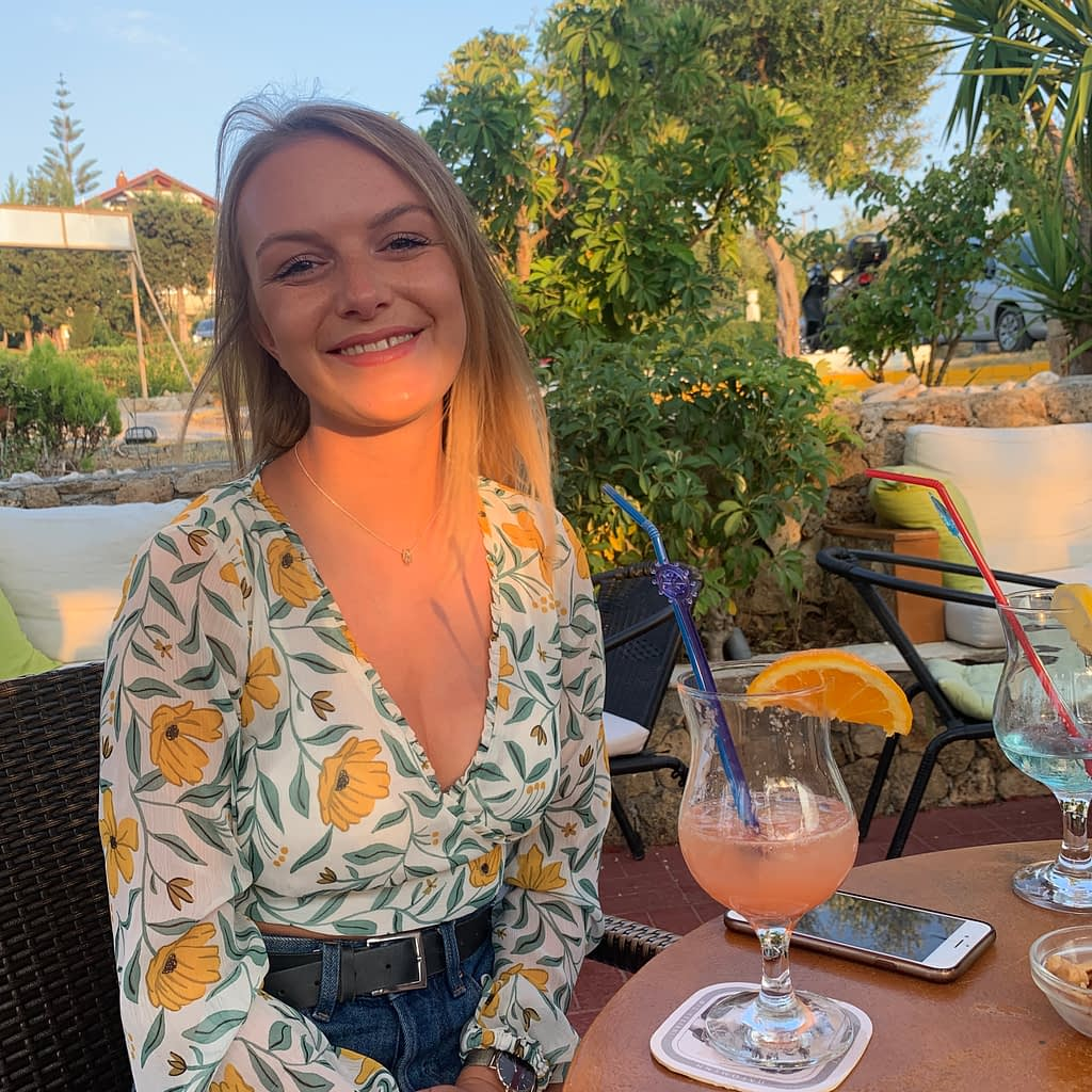 A woman at a restaurant in a flowery top